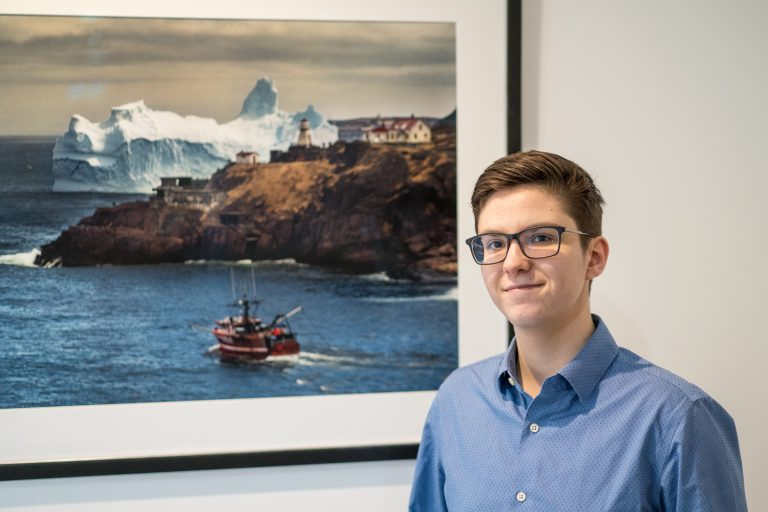 Naval Architect stands in front of photograph of a boat and glacier.