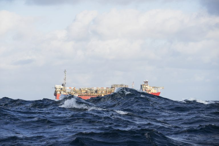 An FPSO floats on the horizon partially obscured by waves during rough weather